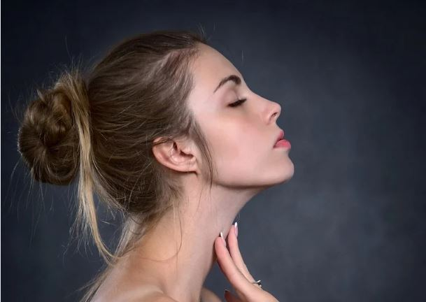 woman side profile with hand on neck, showcasing a skin tightened jawline